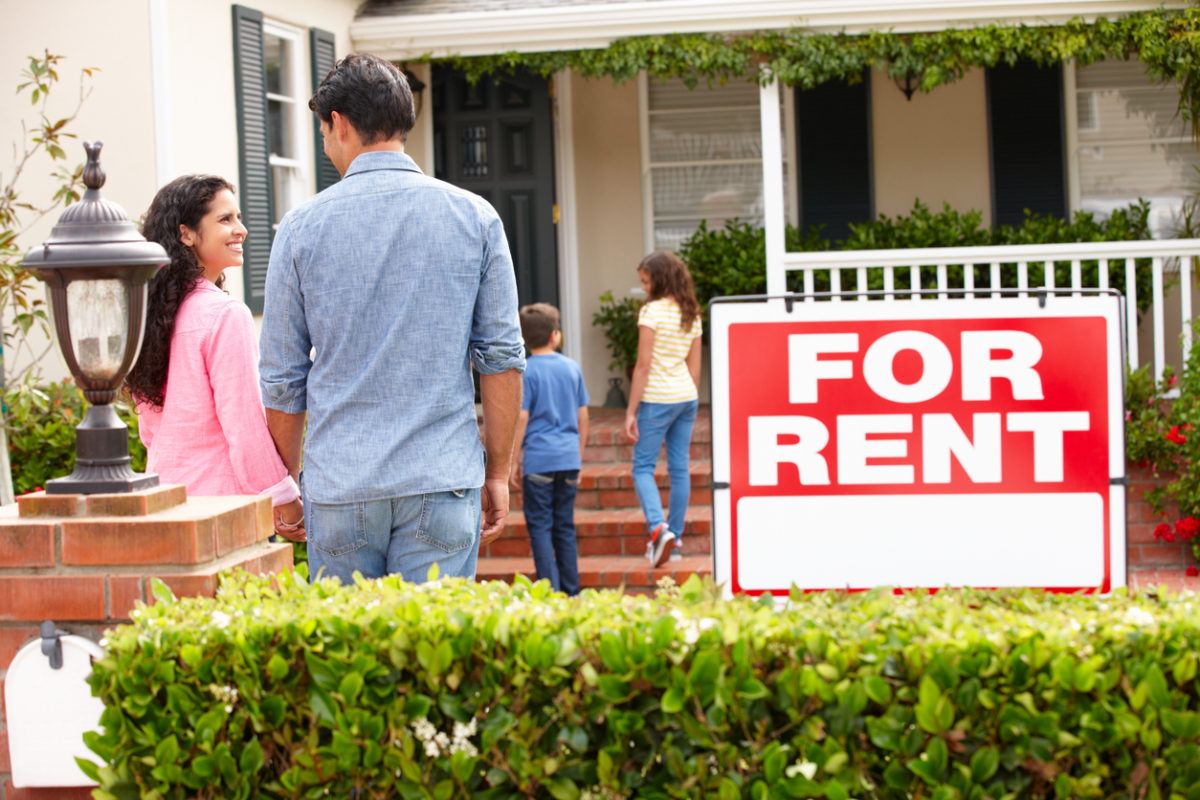 Hispanic family outside home for rent holding hands looking at each other happy