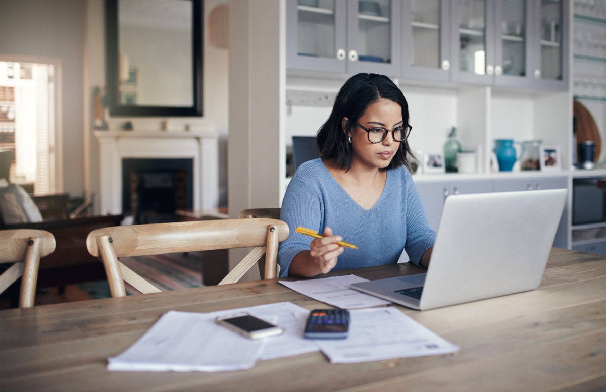 Shot of a young woman using a laptop while working from home and studying up trends in real estate in 2019.