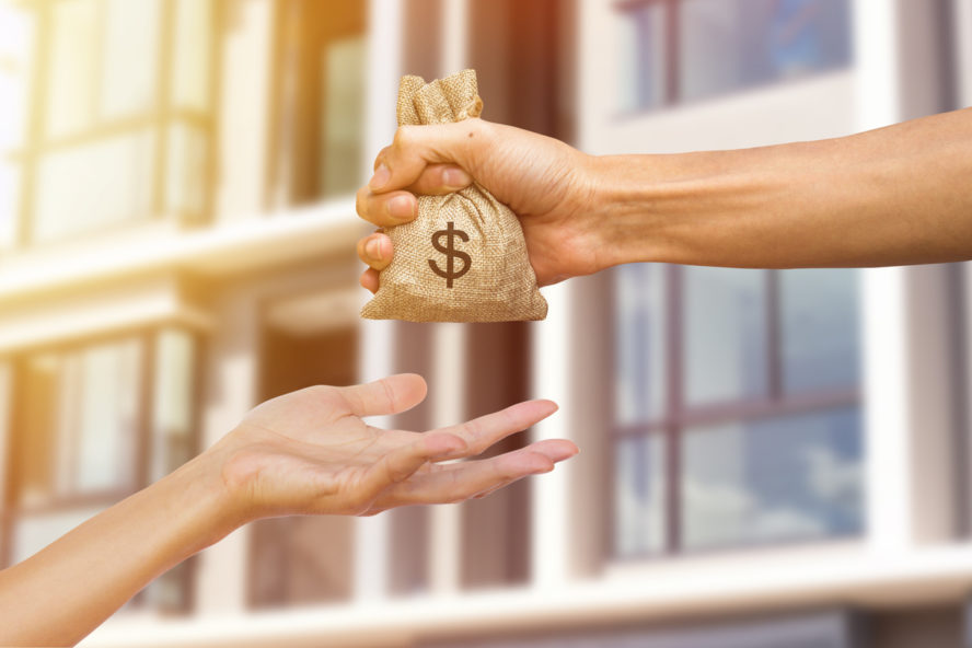A man hand holding a money giving to another person for buying real estate. Loans for real estate concept. Conceptual give money to someone else to exchange real estate.