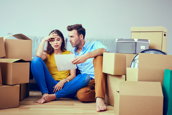 A couple sitting by boxes and worried about moving out of their rental property.