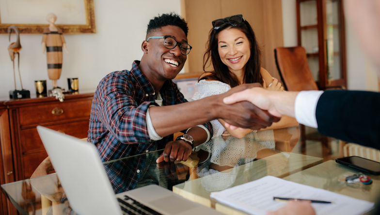 A young couple shaking hands with a cash buyers that buys houses in Fort Lauderdale.