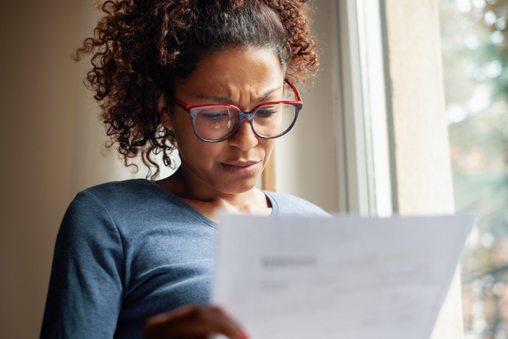 A woman looking over her bills and considering using bankruptcy to stop foreclosure.